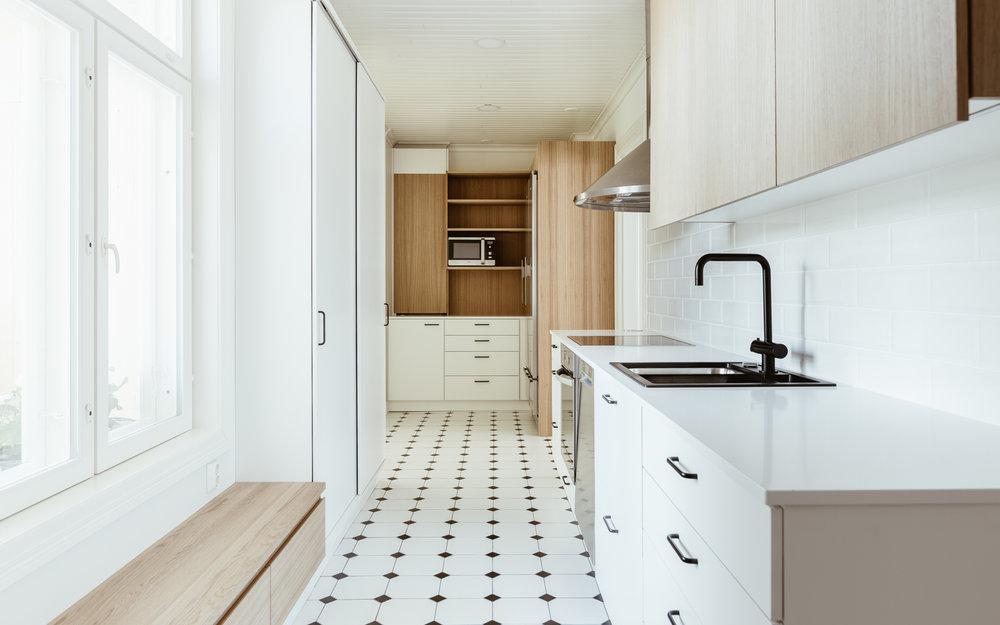 Ikkunan alle tehty penkki laatikoineen ja liukuovikaappi tuovat lisää säilytystilaa kapeaan keittiöön.