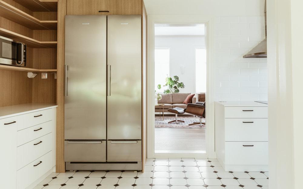 Tammipuinen avohyllykkö ja jääkaapin komero tuovat lämpöä mustavalkoiseen teemaan.