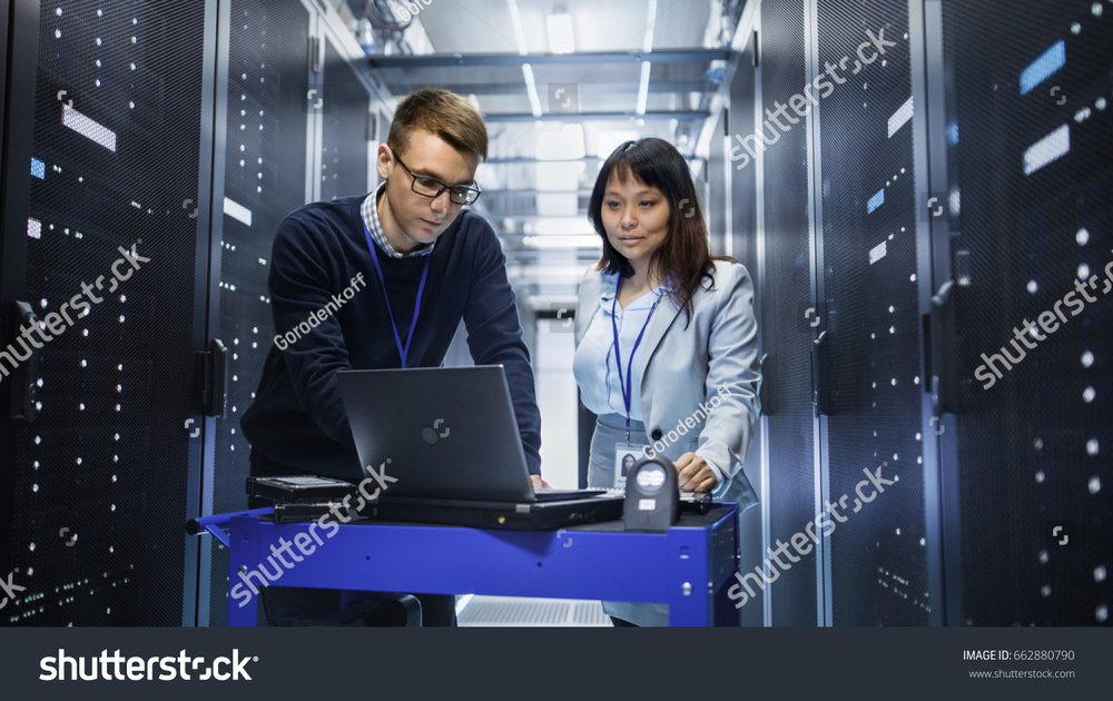 stock-photo-caucasian-male-and-asian-female-it-technicians-working-with-computer-crash-cart-in-big-data-center-662880790.jpg