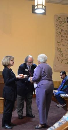 Juli Nelson and Mike Weinman serve communion.jpg