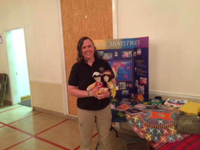 Elena showing various items on her display table. The dolls were made to help children who had experienced the trauma of the earthquake. The photo was taken at the Country Club Congregational United Church of Christ in Kansas City.