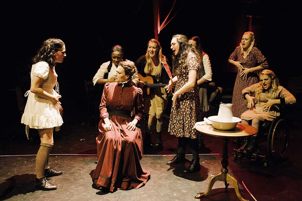 "Sandra Mae Frank, Treshelle Edmond, Natcha Roi (seated), Katie Boeck (on guitar), Lauren Patten, Amelia Hensley (obscured). Alexandra Winter and Ali Stroker in ""Spring Awakening"" at Deaf West Theatre (photo by Tate Tuller)"