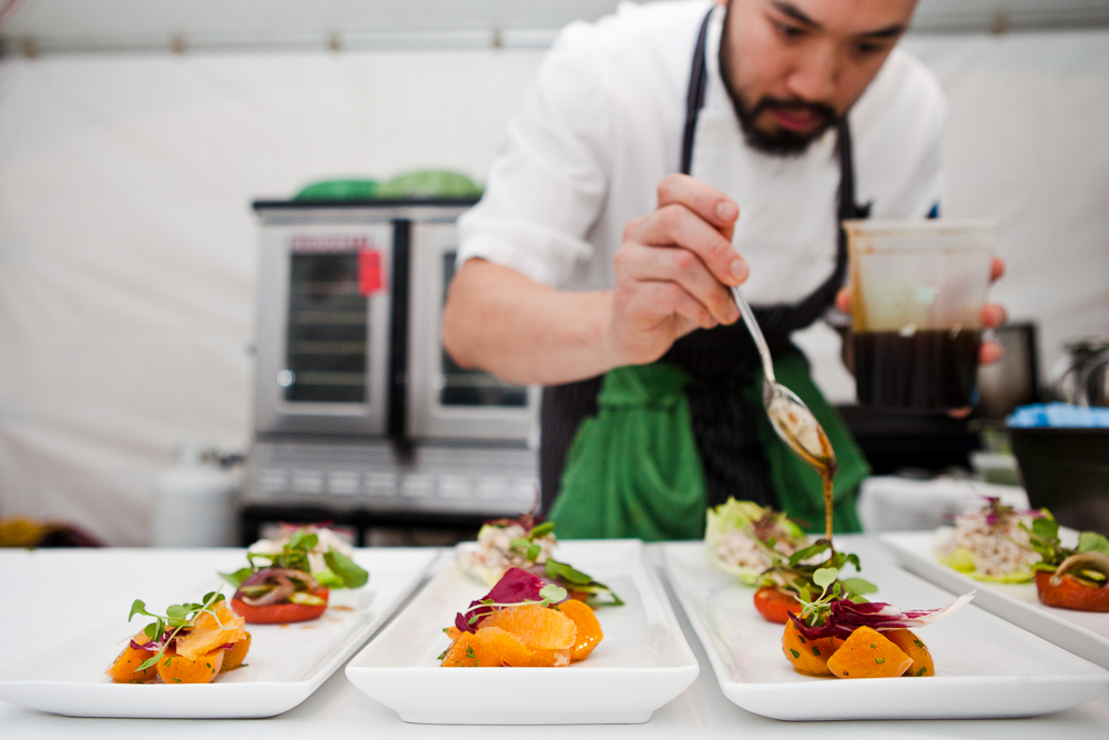 """Live action"" photos from a Dirty Apron catered event of the chefs at work plating dozens of dishes at a time."