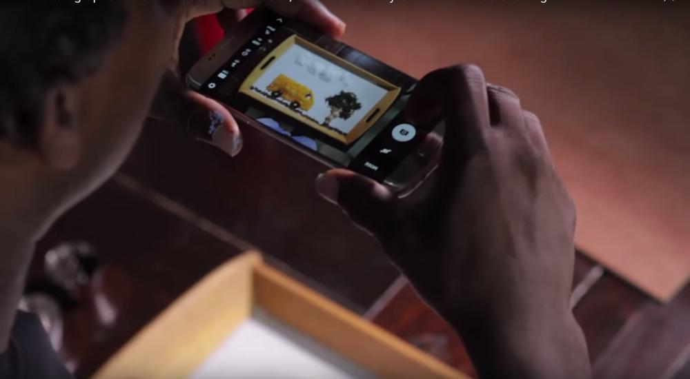 Photographer, Kelechi Amadi-Obi taking a photo of Ozoz Sokoh's Yellow Lagos (22 x 36) using a SAMSUNG GALAXY S7 Edge phone.