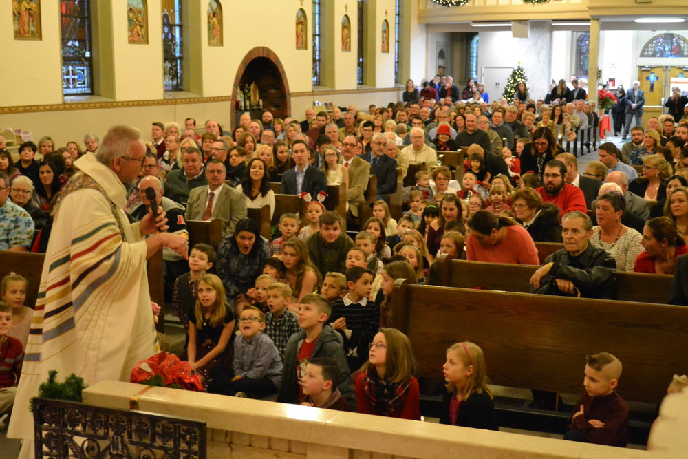 Standing Room Only crowd of 573 at 4:00 pm Christmas Eve Mass in St. Joseph Church. Fr. Tom loves to get our children up close and personal for his homily during the Children's Mass!