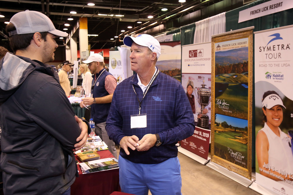 Brendan Sweeney of French Lick Resorts talks to a golfer at the Chicago Golf Show®