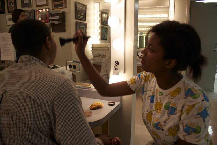 Make-up crew member Naya Foster helps Kennedy Harris get into character before the show.