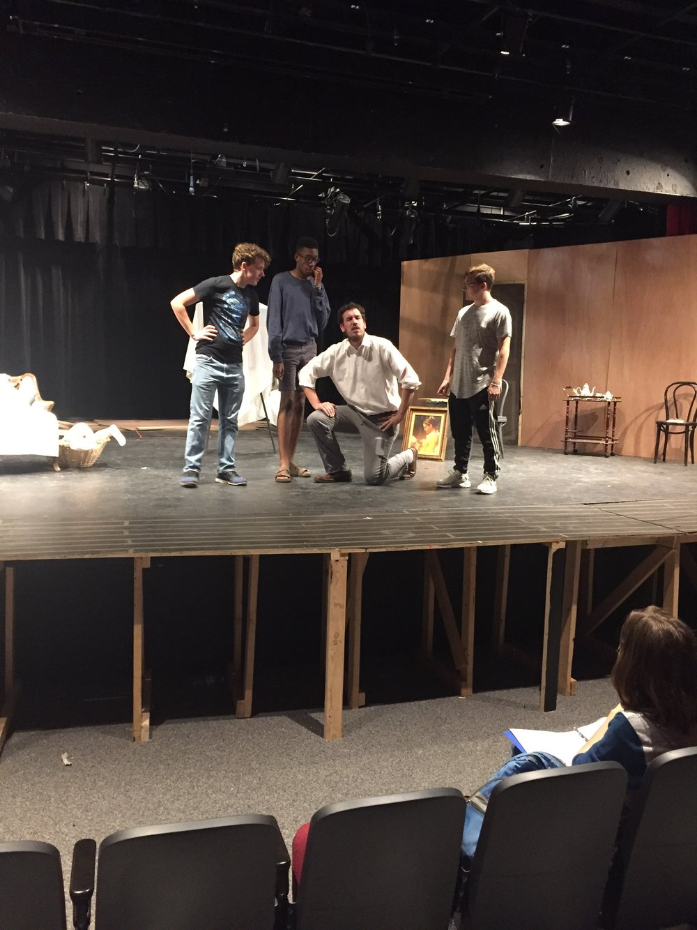 Director Jeff White works with 3 actors onstage.