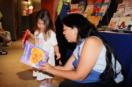 Usborne book vendor helps three-year-old Sidney select a book.