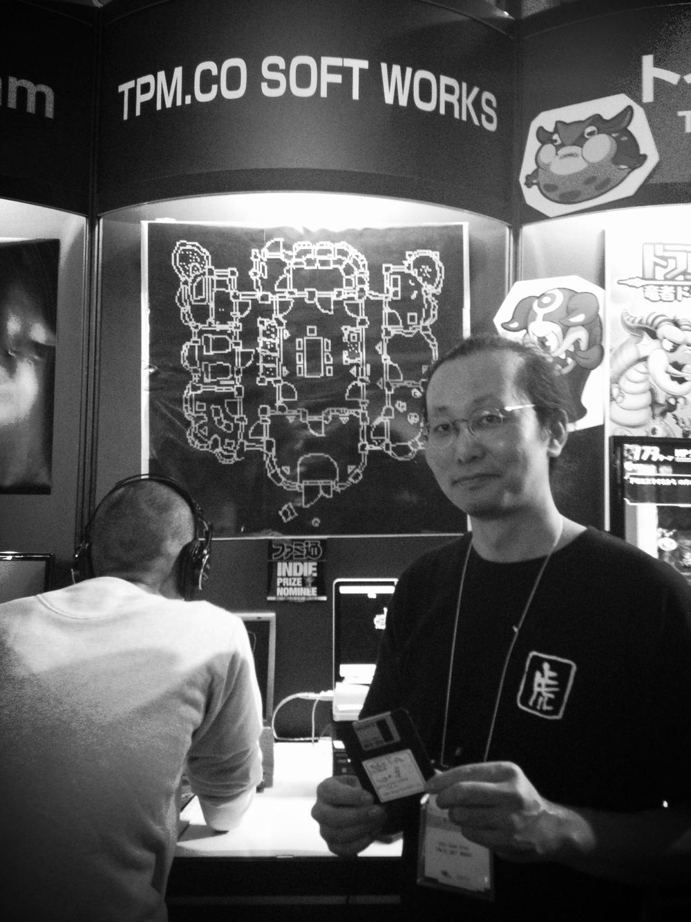 Togo-san, desenvolvedor do TAROTICA VOO DOO segurando um disquete contendo seu jogo.