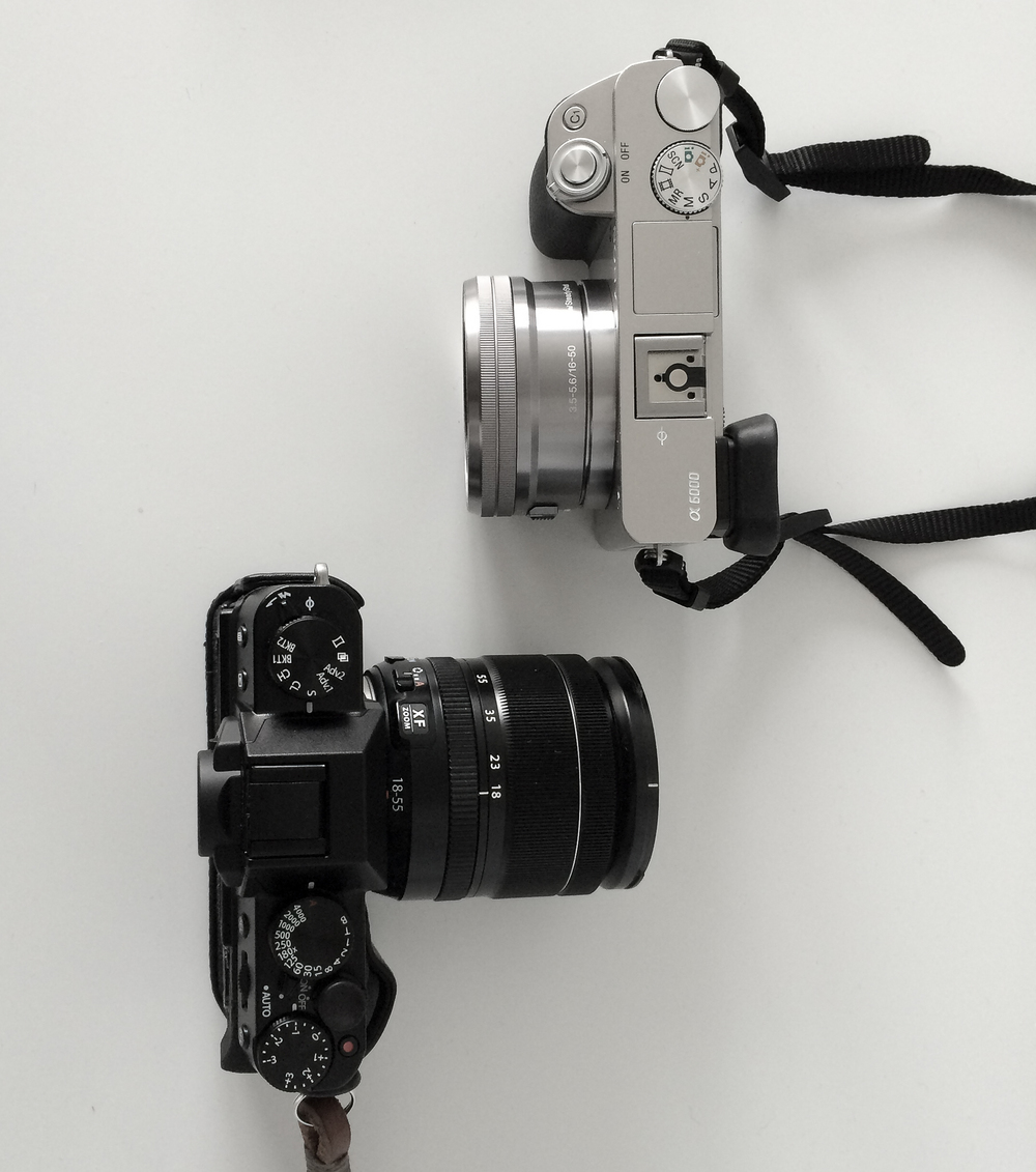 Sony A6000 and Fujifilm X-T10. Note the dedicated shutter speed and exposure compensation dials on the Fuji with aperture setting on the lens, compared to the mode dial and blank programmable dial on the Sony.