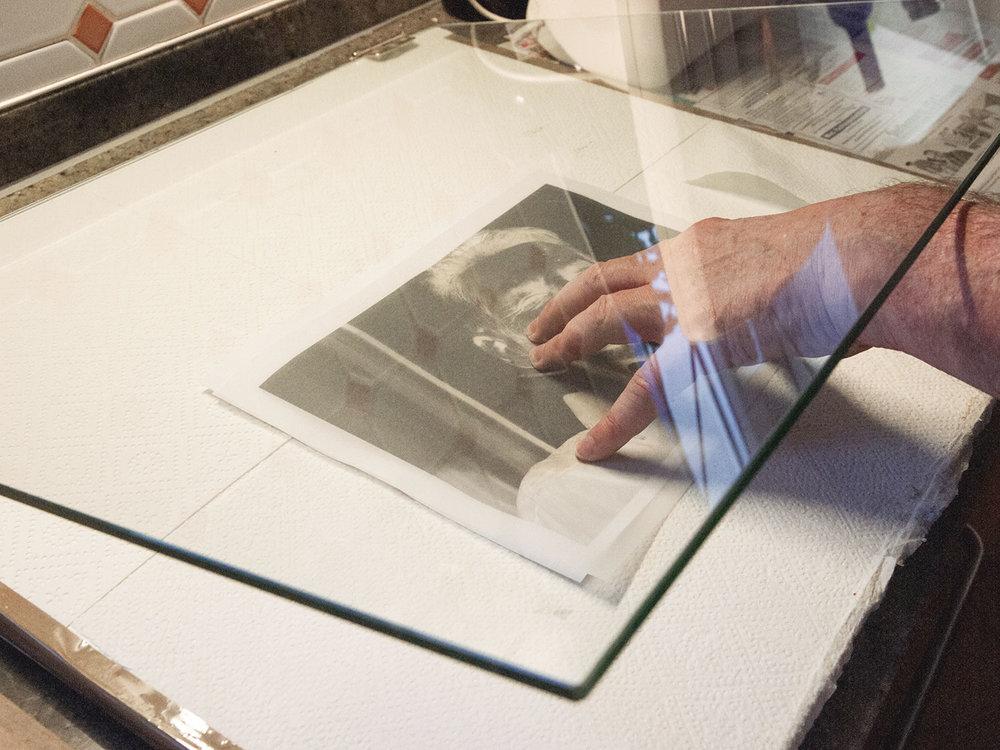 Damit das Negativ auf dem zu belichtenden Papier nicht verrutscht und direkt aufliegt, fixiert man es mit einer Glasplatte.