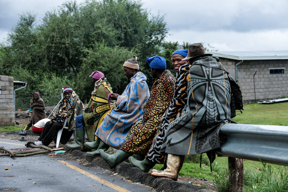 Men in Lesotho wearing traditional Basotho Blankets waiting roadside for the public minibus.
