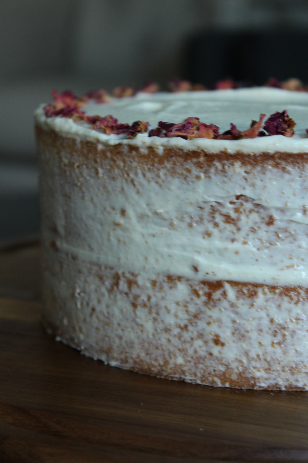 side view: tahini honey cake, cardamom goat cheese frosting, rose petals