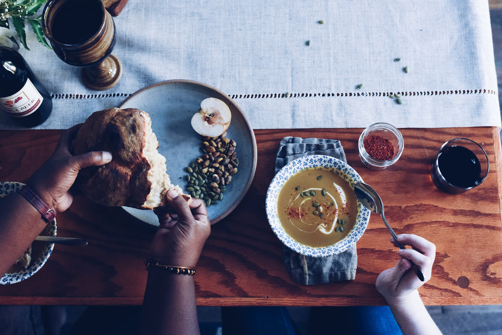 A woman tears a piece of bread off the loaf while the woman next to her dips her spoon into soup