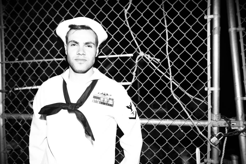 A sailor poses for a portrait one late night outside of the Brass Monkey in NYC