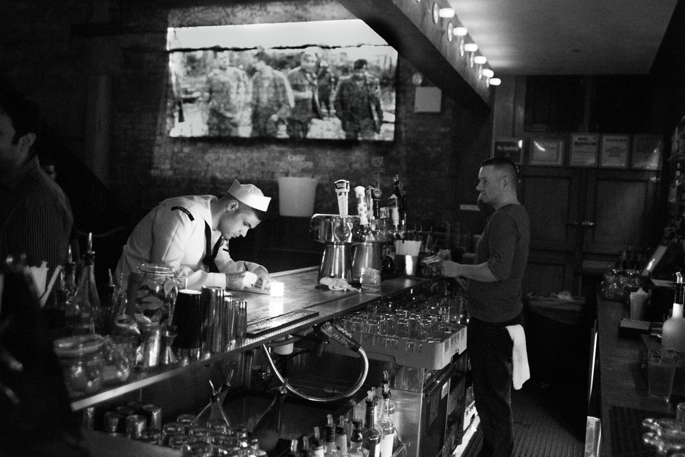 A sailor pays his tab at last call in The Brass Monkey in NYC.