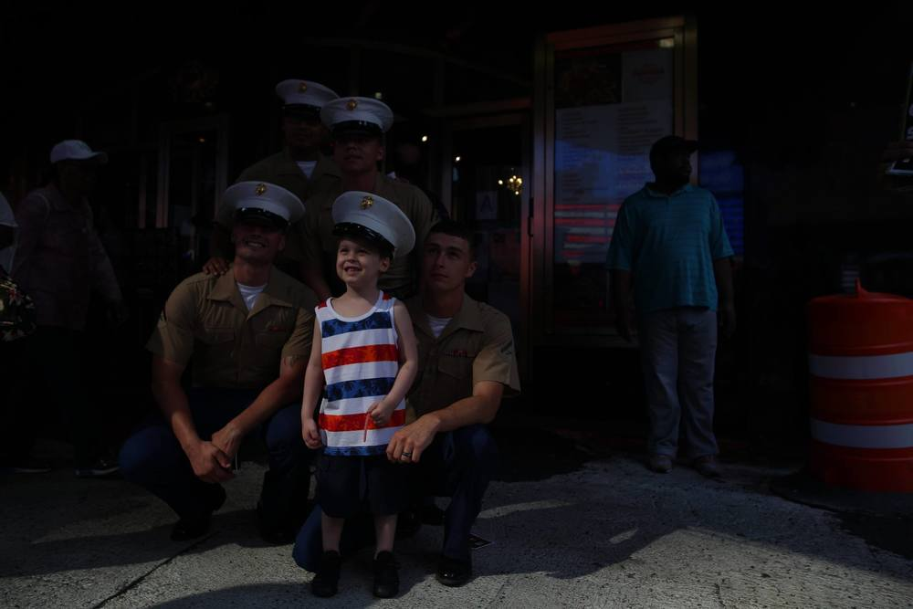 Marines pose for a photo with a child in Times Square, NYC