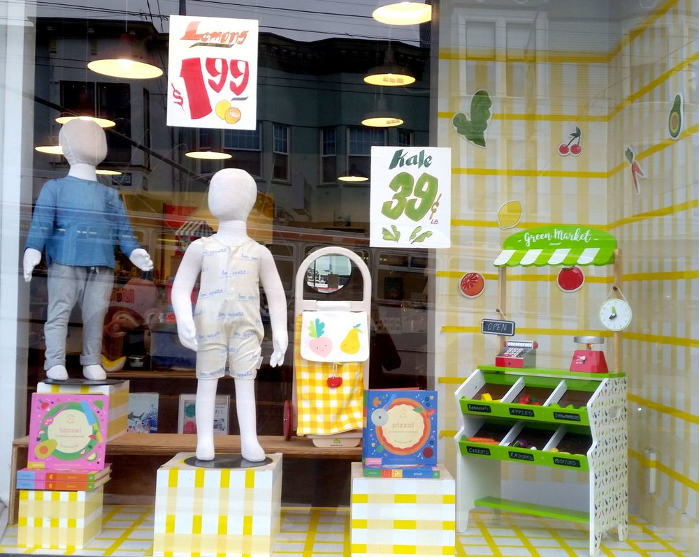 Grocery Store inspired window display, featuring yellow plaid on all surfaces, custom-painted signs and fruit/veggie decals and food themed products. Spring/Summer 2018