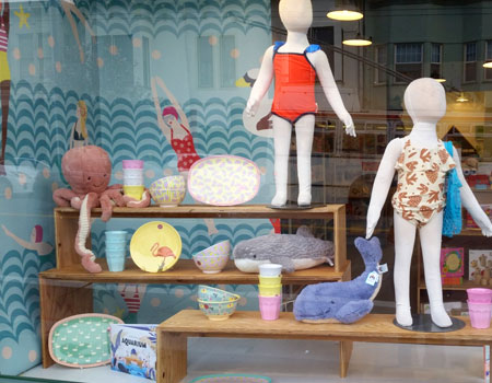 Swim themed window display featuring aquatic stuffed animals, summer fruit dishware and kid's swimwear. Spring/Summer 2018.
