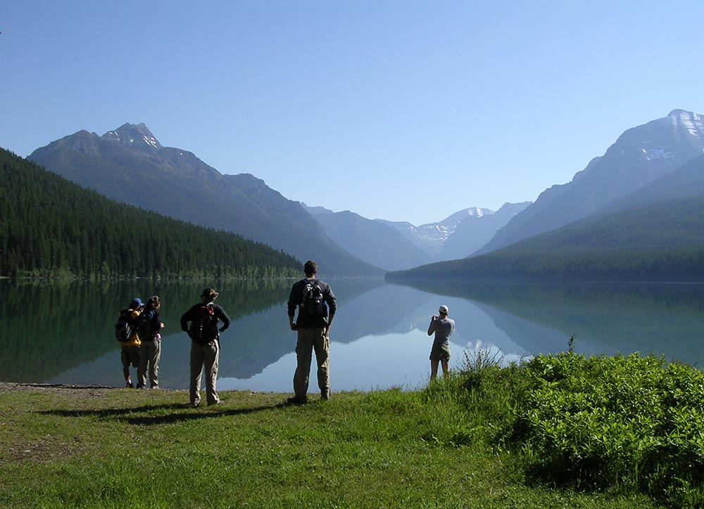 The sky and surrounding ridges reflected in Bowman Lake, along with several other photographers, in mid-summer 2006.  (Image by Emily Benson)