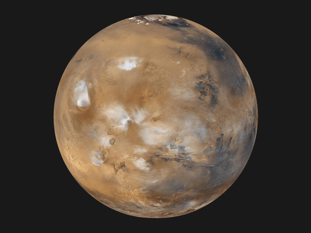 Water also exists in the form of white clouds above the surface of Mars. (Image by NASA/JPL-Caltech/MSSS)
