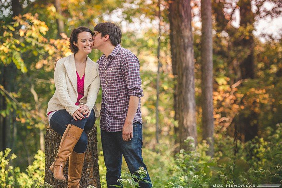 cute kiss while sitting on tree stump