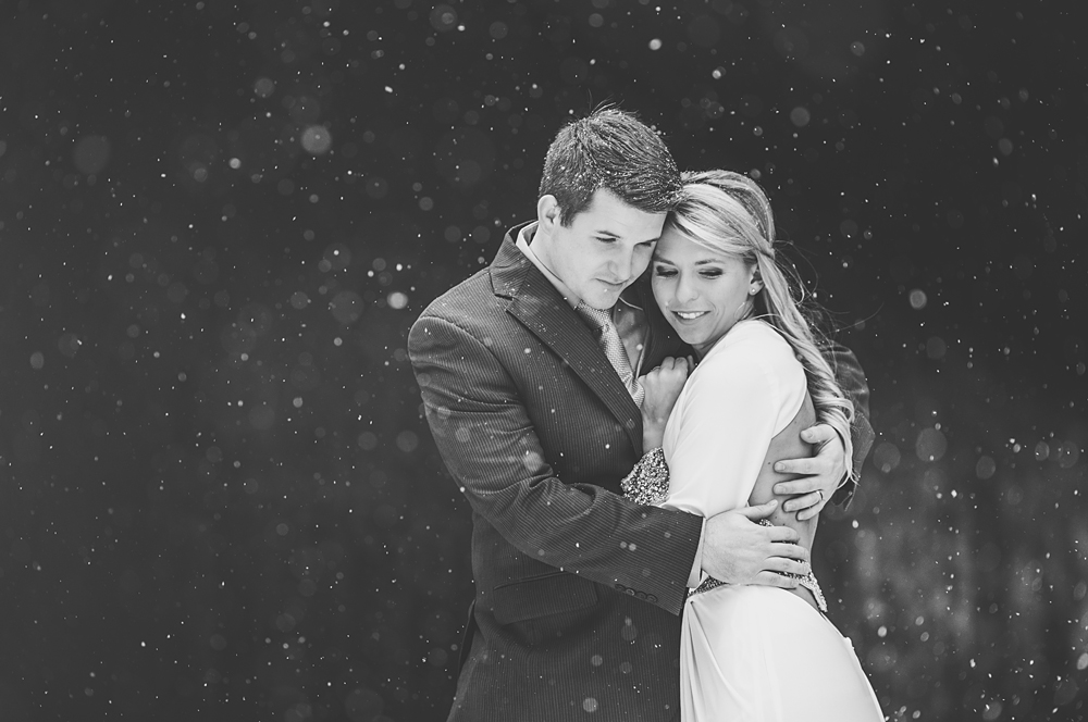 groom keeping his bride warm in the snow