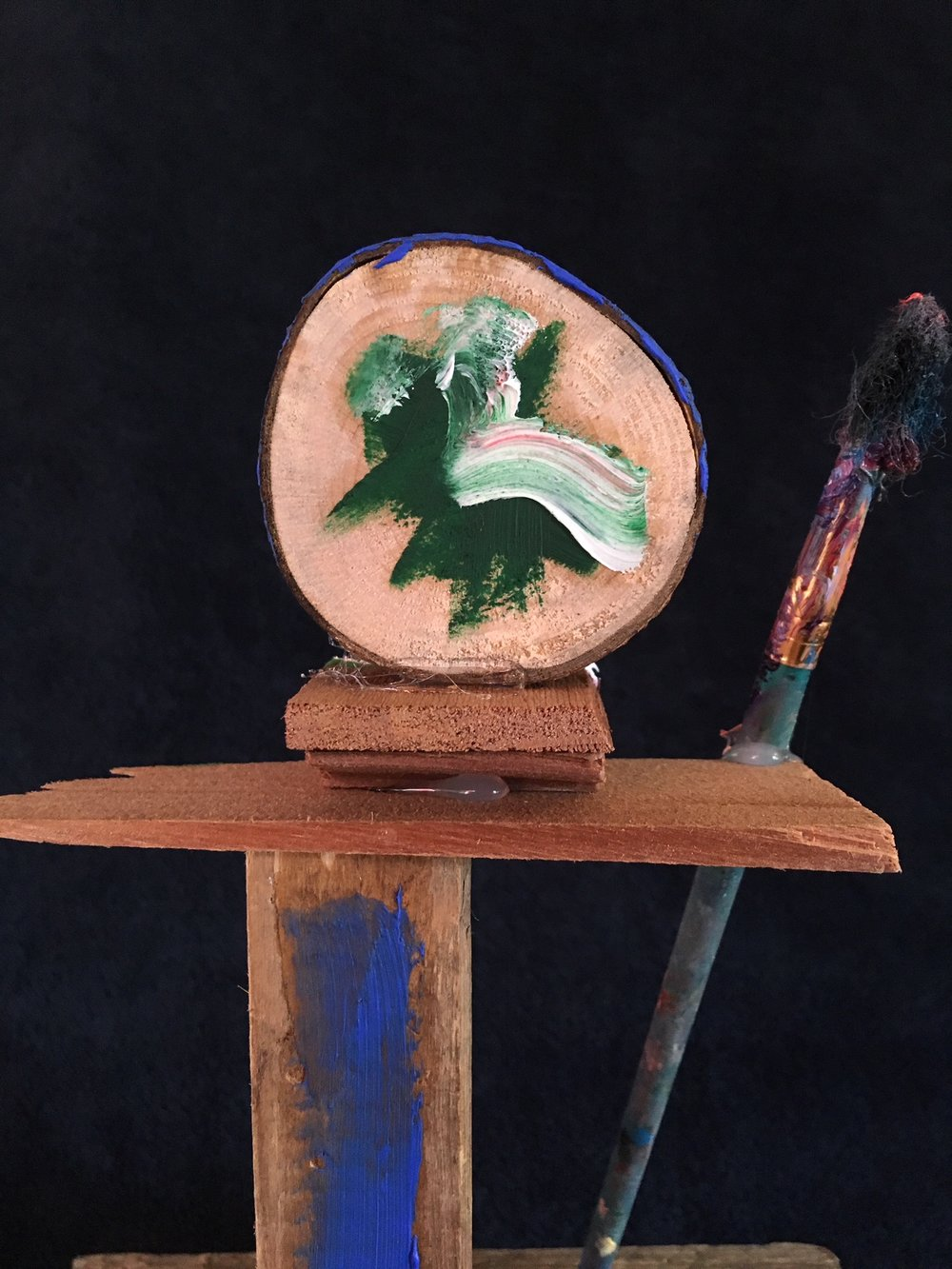 oil paint, paintbrush and wood sculpture on wooden base