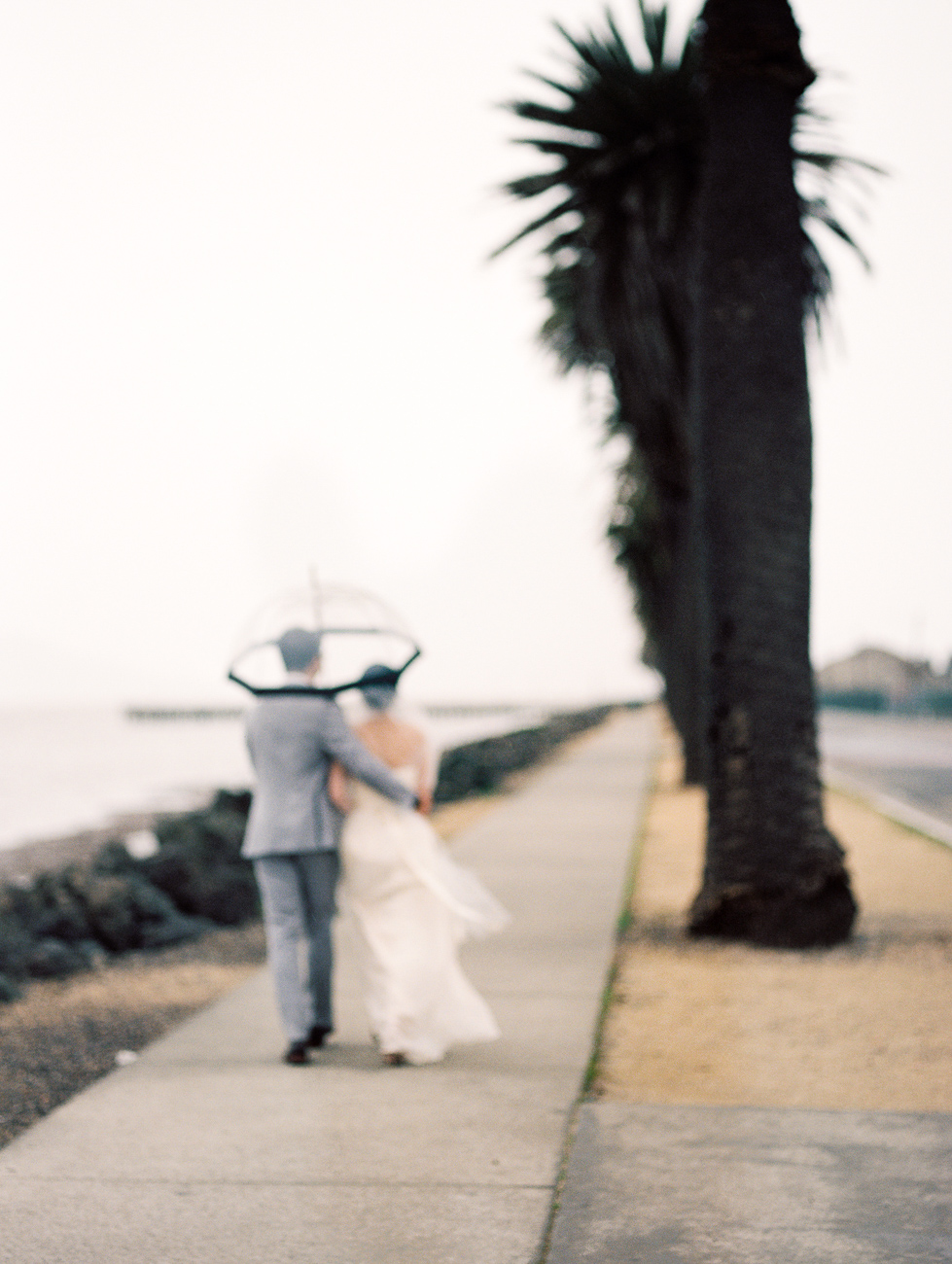 rainy san francisco bay wedding walking with umbrella