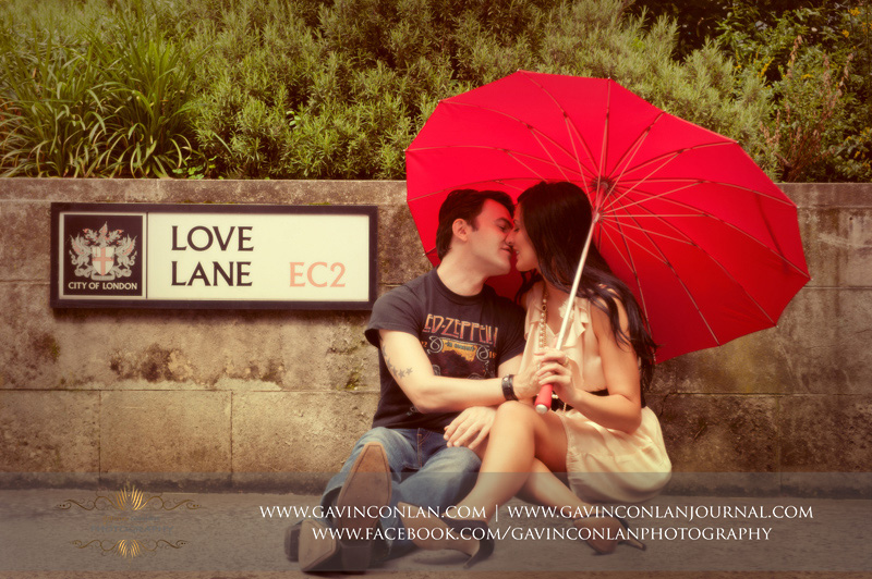 couple sitting on the pavement kissing with red heart shaped umbrella next to the Love Lane EC2 street sign. London engagement photography by  gavin conlan photography Ltd