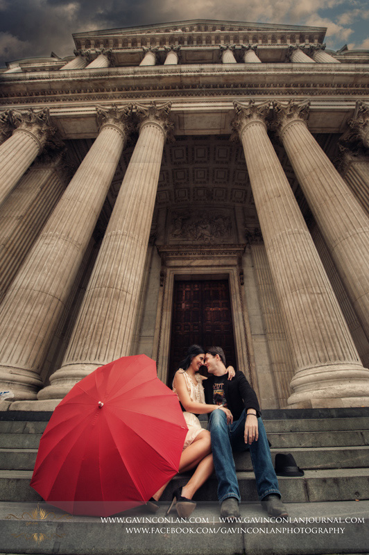 creative portrait of the couple sitting on the steps of St Pauls Cathedral with a red heart shaped umbrella next to them. London engagement photography by  gavin conlan photography Ltd