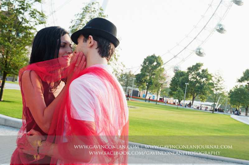 fun couple portrait of them kissing as they play with a red scarf outside the London Eye. London engagement photography by  gavin conlan photography Ltd