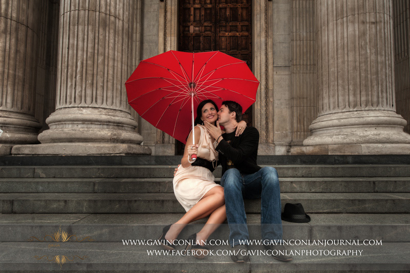 couple sitting on the steps of St Pauls Cathedral with a red heart shaped umbrella. London engagement photography by  gavin conlan photography Ltd