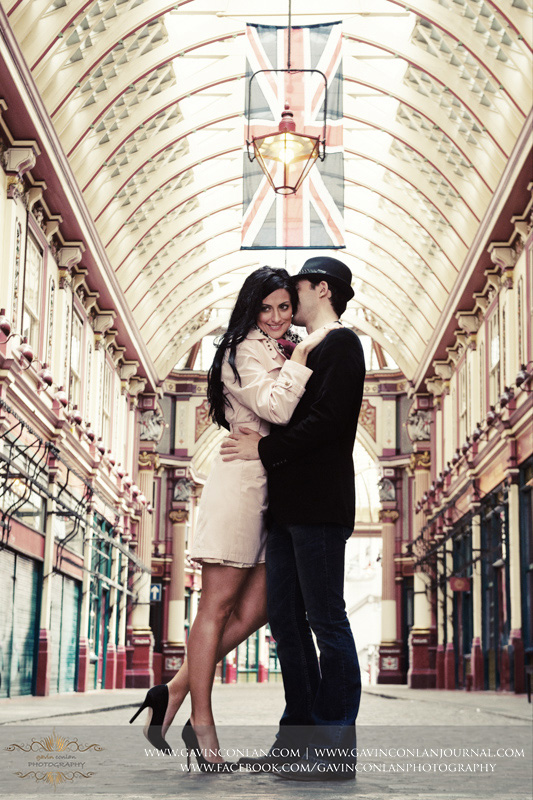 couple enjoying a romantic moment under the British flag at Leadenhall Market. London engagement photography by  gavin conlan photography Ltd