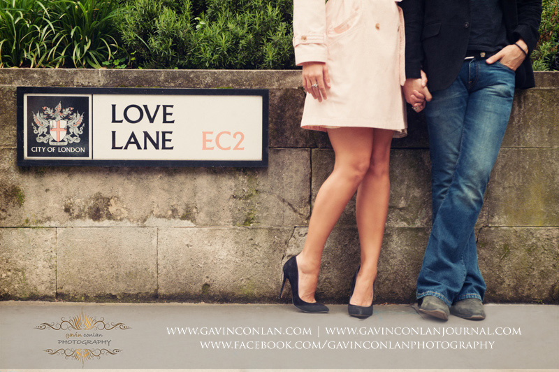 creative portrait of the couple standing on Love Lane EC2. London engagement photography by  gavin conlan photography Ltd