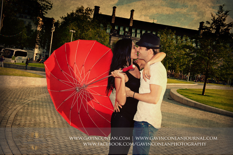 creative and fun couple portrait playing with the red heart shaped umbrella whilst kissing. London engagement photography by  gavin conlan photography Ltd