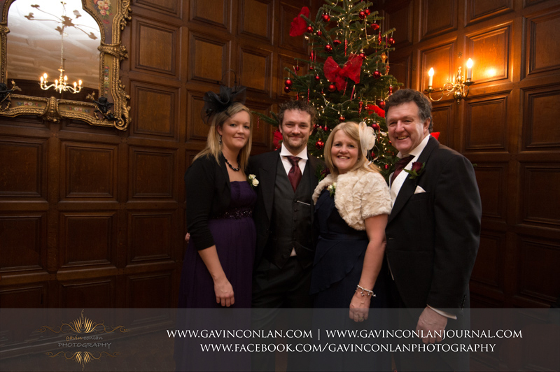 a portrait of the groom with his parents and sister in front of the Christmas tree.Wedding photography at Hengrave Hall by gavin conlan photography Ltd