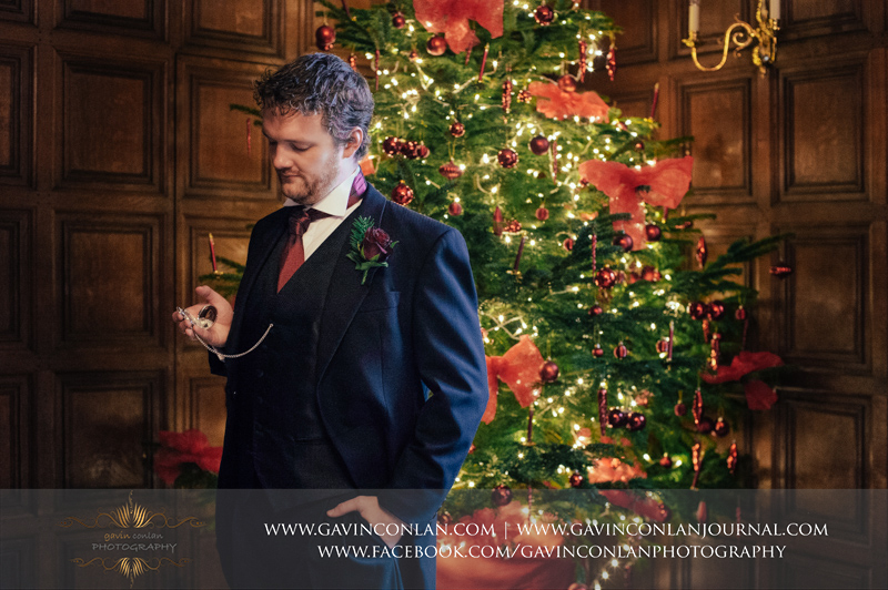 beautiful portrait of the groom looking at his pocket watch standing in front of the Christmas tree. Wedding photography at Hengrave Hall by gavin conlan photography Ltd