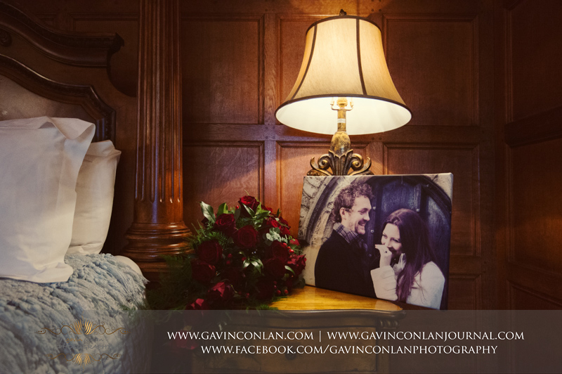 beautiful detail photograph of the bridal bouquet and their engagement photograph in the bridal suite. Wedding photography at Hengrave Hall by gavin conlan photography Ltd