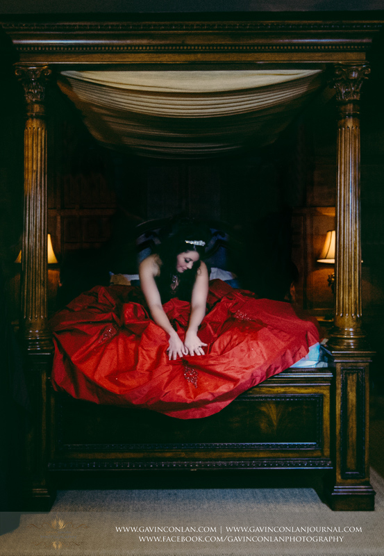 create portrait of the gorgeous bride in her red wedding dress on the bed in the bridal suite. Wedding photography at Hengrave Hall by gavin conlan photography Ltd