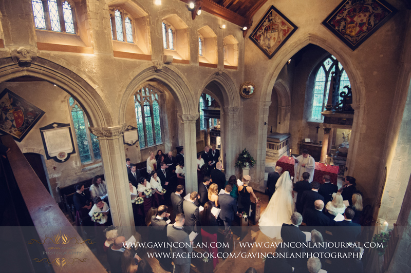 creative portrait of the bride and groom during their ceremony inside the stunning Church at Hengrave Hall. Wedding photography at Hengrave Hall by gavin conlan photography Ltd