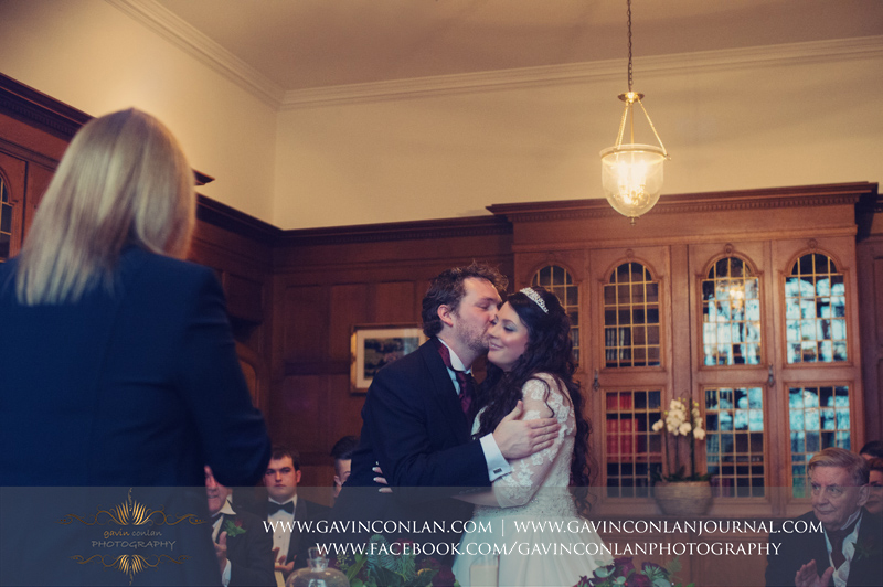 portrait of the groom kissing his new wife on the cheek at the end of their official ceremony. Wedding photography at Hengrave Hall by gavin conlan photography Ltd