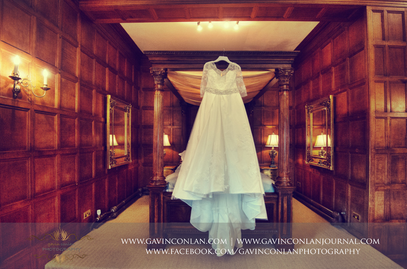 a beautiful detail portrait of the brides wedding dress hanging in front of the four poster bed in the bridal suite. Wedding photography at Hengrave Hall by gavin conlan photography Ltd