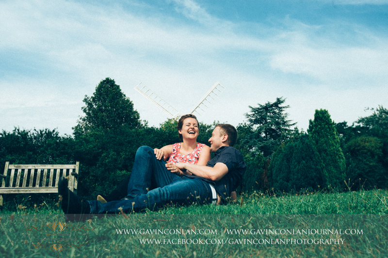 couple sitting and laughing on the grass in Finchingfield.  Essex engagement photography by  gavin conlan photography Ltd