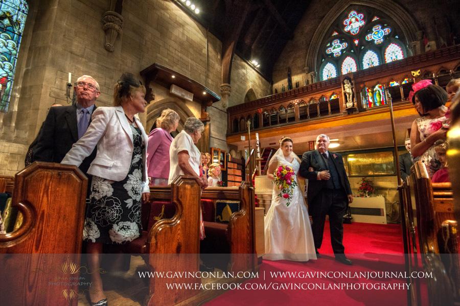 bride entering.Wedding photography at All Saints Cranham by gavin conlan photography Ltd