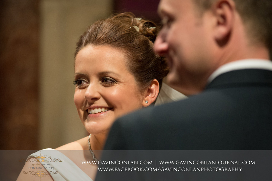 bride and groom looking back at guest. Wedding photography at  All Saints Cranham  by  gavin conlan photography Ltd
