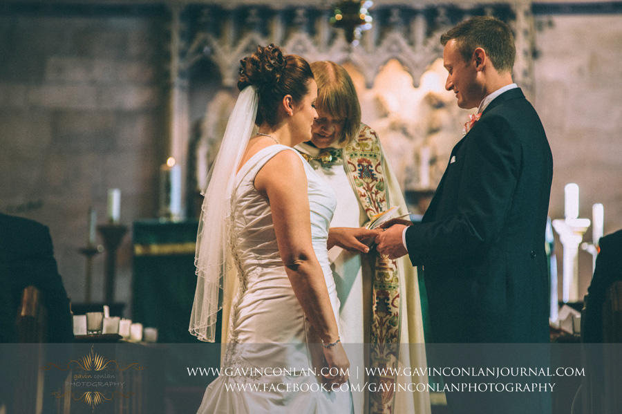 groom putting ring on brides finger. Wedding photography at  All Saints Cranham  by  gavin conlan photography Ltd