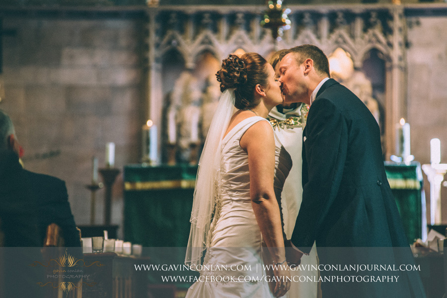 bride and groom first kiss. Wedding photography at  All Saints Cranham  by  gavin conlan photography Ltd
