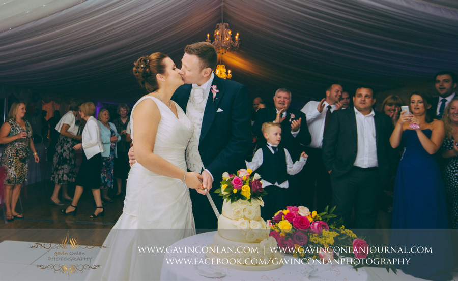 bride and groom cutting the cake. Wedding photography at  Moor Hall Venue  by  gavin conlan photography Ltd